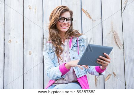 Beautiful woman using tablet pc against wooden planks