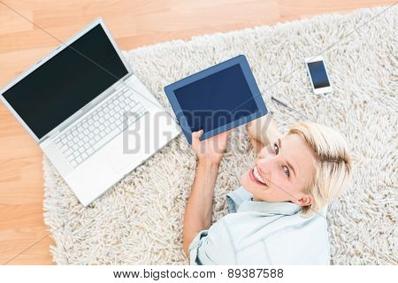 Pretty blonde woman lying on the floor and using her tablet in the living room