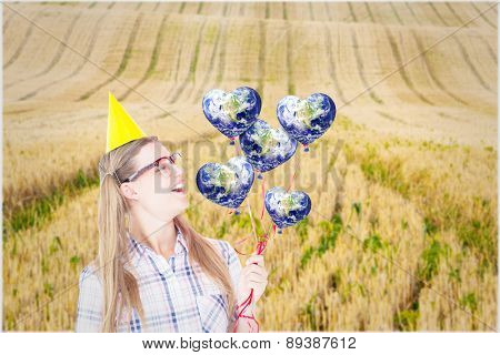 Geeky hipster holding red balloons against rural fields