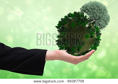 Businesswomans hand presenting against green abstract light spot design