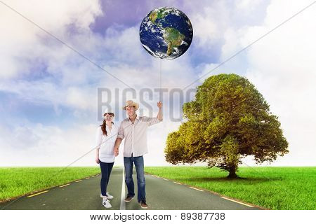 Smiling couple both wearing hats against road leading out to the horizon