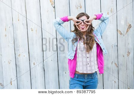Pretty woman looking thought fingers against wooden planks