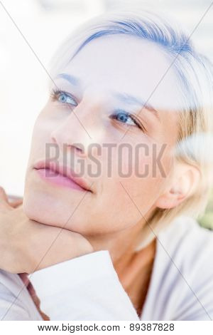 Smiling blonde woman looking through the window in the bedroom