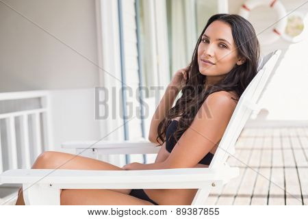 Beautiful young woman relaxing on sun lounger
