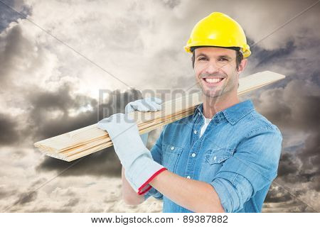Happy carpenter carrying wooden planks against blue sky with white clouds