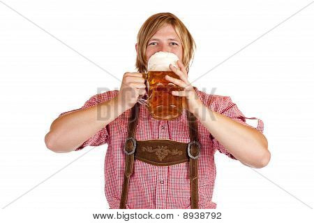 Happy Bavarian man drinks out of oktoberfest beer stein.