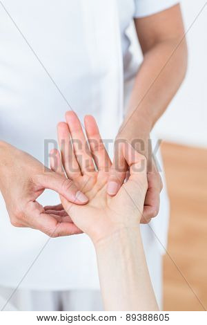 Physiotherapist examining her patients hand in medical office