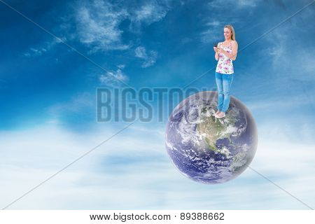 Smiling blonde sending a text message against blue sky