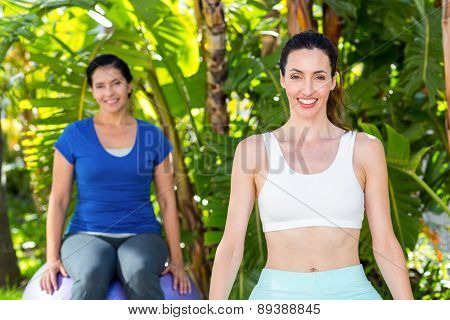 Smiling woman and her trainer looking at camera on a sunny day