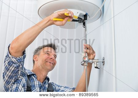 Male Plumber Repairing Electric Boiler