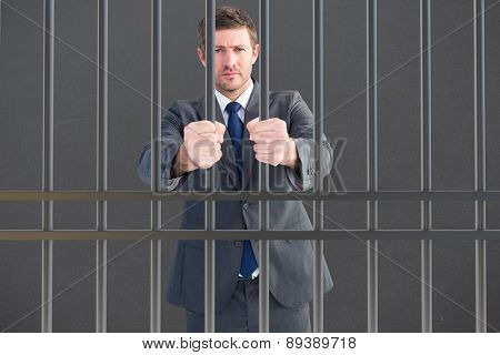 Businessman holding his hands out against grey