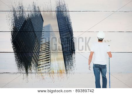 Painter against low angle view of skyscrapers