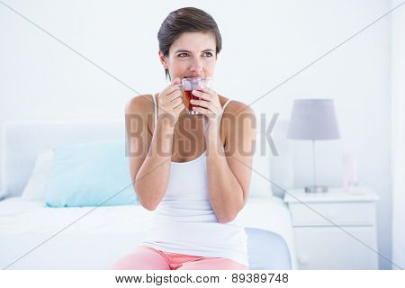 Happy woman drinking cup of tea at home in the bedroom