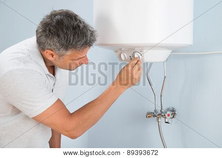 Man Adjusting Temperature Of Electric Boiler