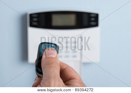 Person Using Remote Control To Disarm The Security System
