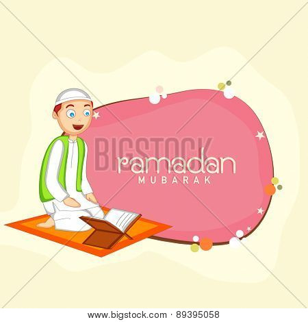 Cute Muslim boy reading holy book Quran Shareef on occasion of Islamic holy month of prayers, Ramadan Kareem celebration.