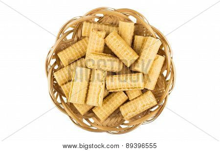 Heap Of Wafer Rolls In Wicker Basket Isolated On White