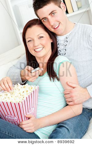 Hugging Couple Eating Popcorn And Watching Television Lying On The Sofa