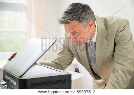 Businessman Looking At Photocopy Machine
