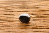 stock photo of obsidian  - Obsidian on oak wood surface - JPG