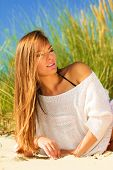 foto of dune grass  - Young woman female model posing outdoor on background of dunes sky and grass - JPG