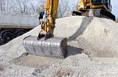 pic of excavator  - Close up of excavator bucket scooping gravel from pile for road construction - JPG