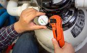 stock photo of manometer  - Closeup shot of plumber installing manometer on pipe - JPG