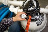 pic of manometer  - Closeup shot of plumber checking manometer on big hydraulic pump - JPG