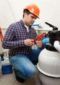 stock photo of groundwater  - Young plumber installing manometer on high pressure barrel - JPG
