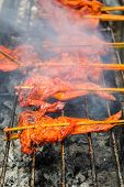 picture of flame-grilled  - Thai Chicken grilled over flames on the flaming grill - JPG