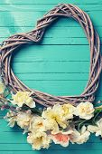 foto of daffodils  - Fresh yellow daffodils willow branches and decorative heart on turquoise painted wooden planks - JPG