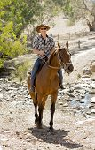 image of horse-riders  - young horse instructor or cattleman riding the animal wearing sunglasses cowboy hat and rider boots looking cool while taking a ride at countryside summer landscape