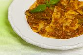 stock photo of shredded cheese  - Cheese and spinach stuffed ravioli pasta with tomato sauce and parmesan cheese - JPG