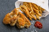 pic of crisps  - Crisp crunchy golden chicken wings with French fries on a dark table - JPG