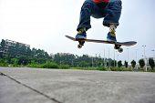 pic of skateboarding  - young skateboarder doing skateboarding trick ollie outdoor  - JPG