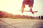 image of skateboarding  - young skateboarder  legs doing skateboarding trick ollie outdoor  - JPG