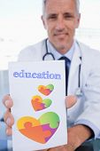 image of prescription pad  - The word education and portrait of a male doctor showing a blank prescription sheet against autism awareness heart - JPG
