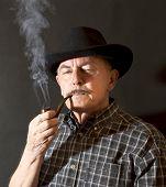 foto of hillbilly  - Cowboy in black hat smoking a pipe - JPG