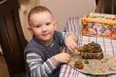stock photo of molding clay  - the little boy sits at a table and molds products from plasticine - JPG