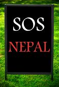 picture of sos  - SOS NEPAL message on sidewalk blackboard sign against green grass background - JPG