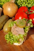 foto of baguette  - Slice of baguette with tuna fillet garnished with lettuce onion tomato and pickles on a wooden board - JPG