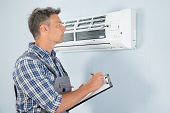 pic of air conditioner  - Portrait Of Male Technician Holding Clipboard Looking At Air Conditioner - JPG