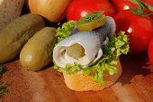 picture of baguette  - Baguette slice with sour herring pickled herring garnished with lettuce gerkin - JPG