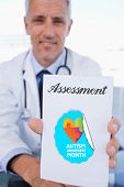 stock photo of prescription pad  - The word assessment and portrait of a male doctor showing a blank prescription sheet against autism awareness month - JPG