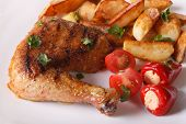 stock photo of thighs  - Grilled chicken thighs fried potatoes and vegetables on a plate close - JPG