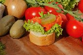 pic of baguette  - Slice of baguette with pollock fillet garnished with lettuce onion tomato and pickles on a wooden board - JPG