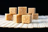 stock photo of sugar cube  - Cubes of cane sugar on the mat on the black background - JPG