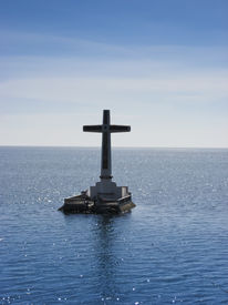 stock photo of camiguin  - large crucifix marking the underwater sunken cemetery of the coast of camiguin island near mindanao in the philippines