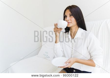 Beautiful Stunning Woman Sipping Coffee From A White Cup