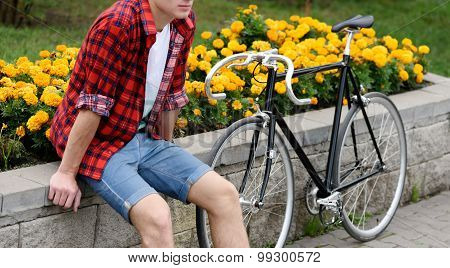 Hipster man with bicycle resting over flowerbed withal yellow flowers